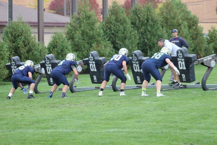 Coach Salm helps the football team during practice.