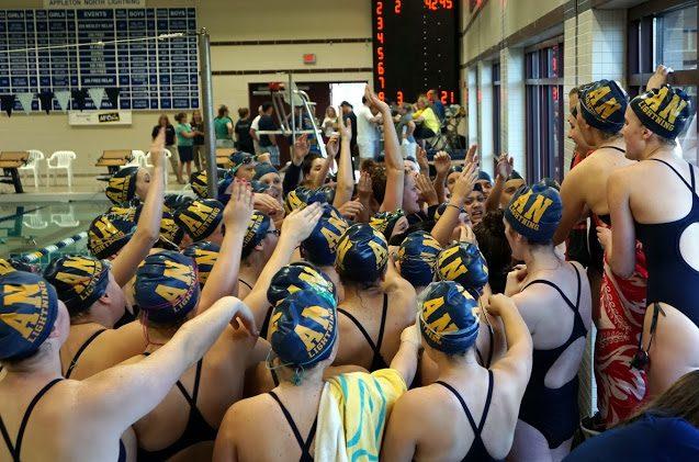 The girls swim team getting pumped up before a meet.