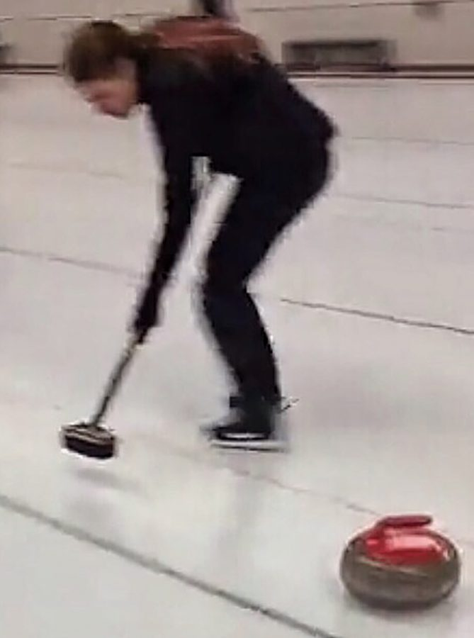 Sophomore Sarah Fleming, in this action shot taken from Noctiluca's Snapchat, sweeps the ice as she leads the rock to the house.