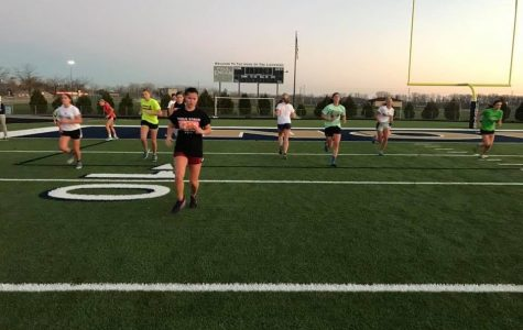 The 2016-17 Girls' Basketball team trains on the football field.